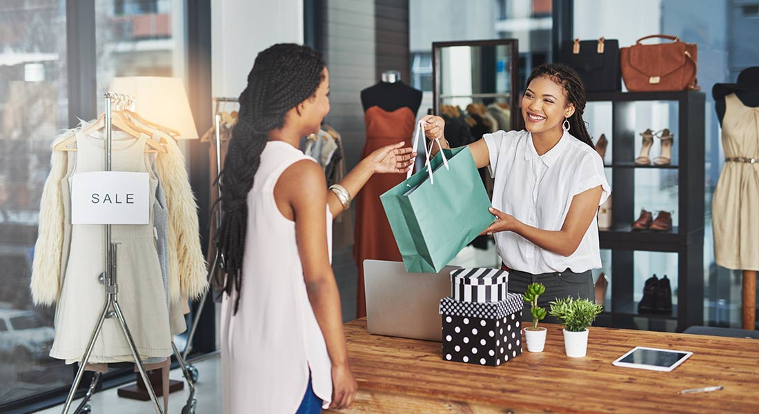 smiling woman making a purchase at a clothing boutique