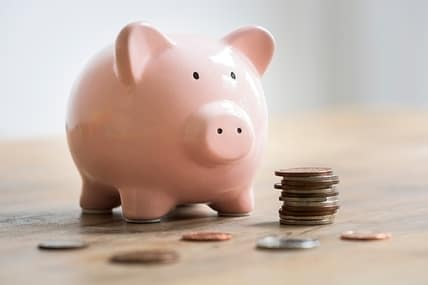 pink piggy bank with lots of coins
