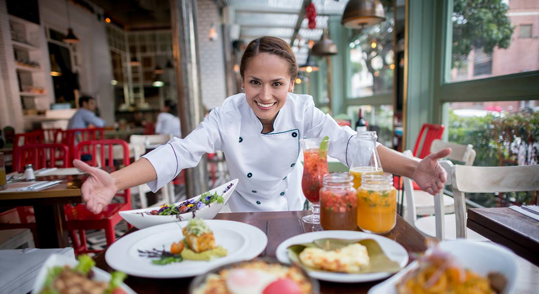 Smiling female restaurant owner at a table with food
