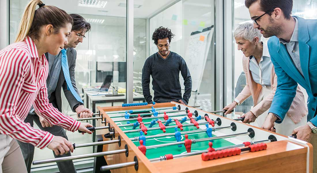 group of employees playing table football