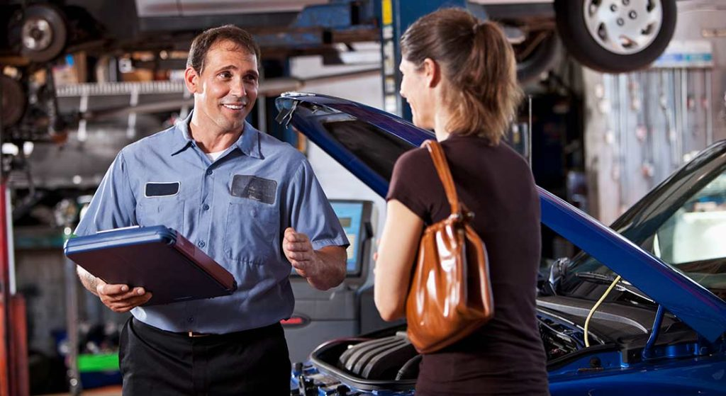auto repair shop owner with female customer
