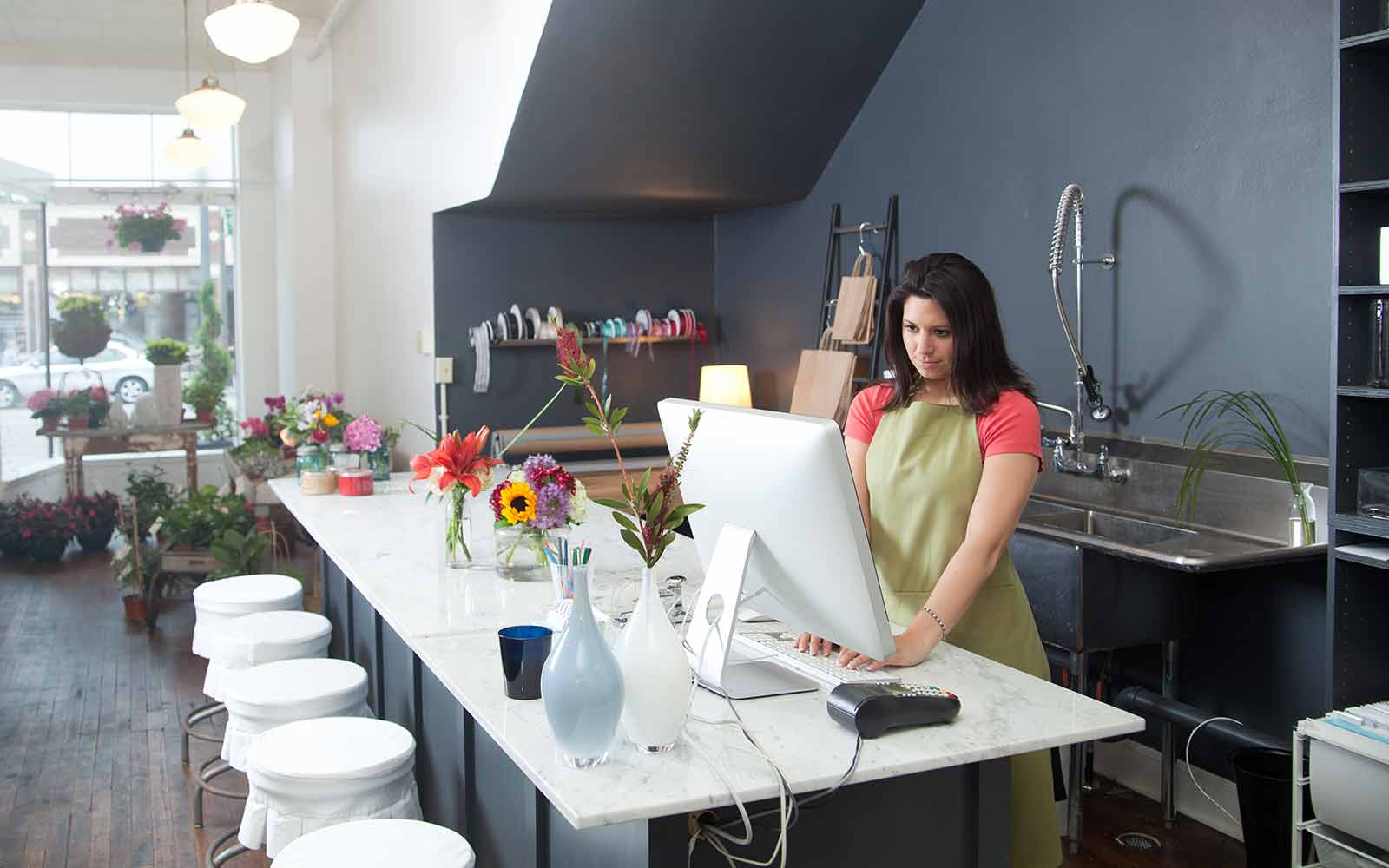 female florist reading business cash advance faq on computer