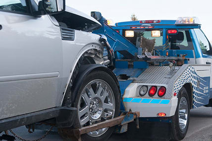 tow truck hauling a damaged vehicle