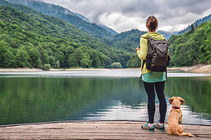 woman hiking with her dog in the mountains