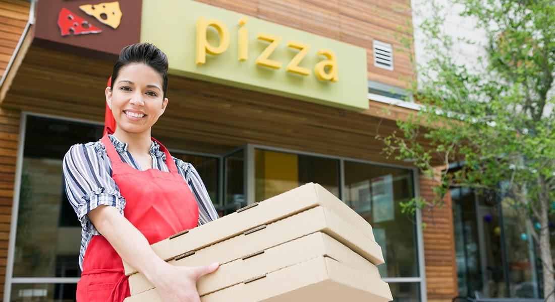 female pizza franchise owner carrying pizzas