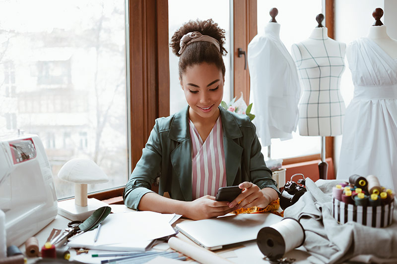 female dressmaker checking messages on her mobile phone