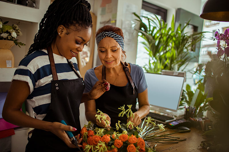 two female florists building a bouquet of orange flowers