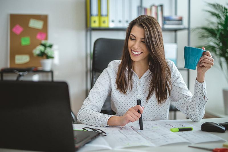female entrepreneur having coffee at her desk