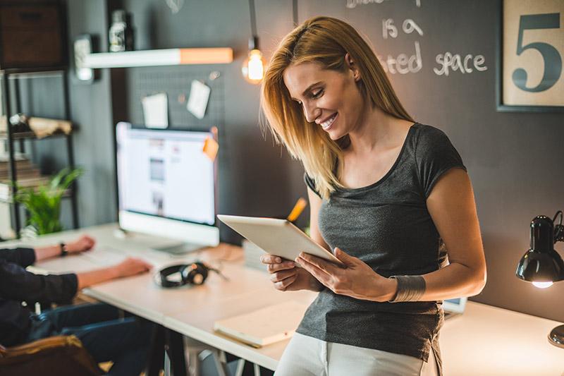 blonde female entrepreneur using a tablet