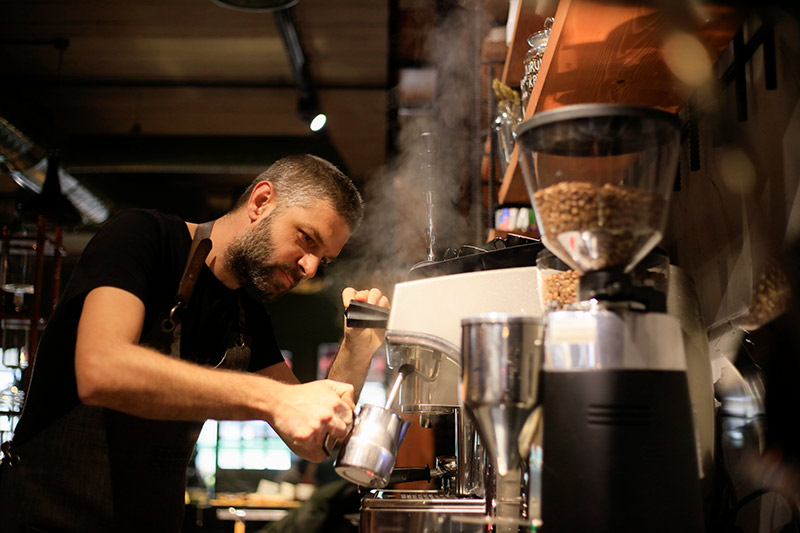 male barista steaming milk for a cafe latte