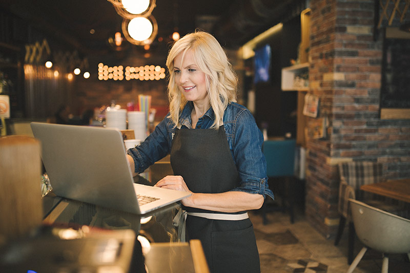 blonde female restaurant owner using a laptop computer