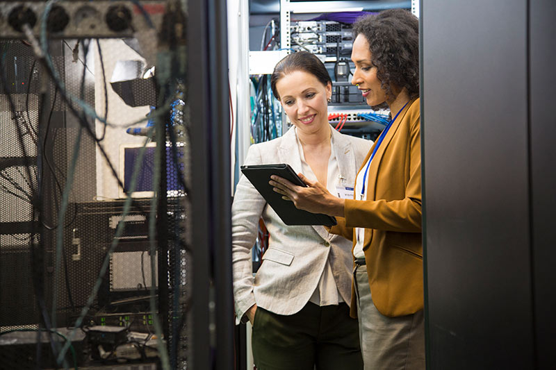 two female employees working in a computer server room