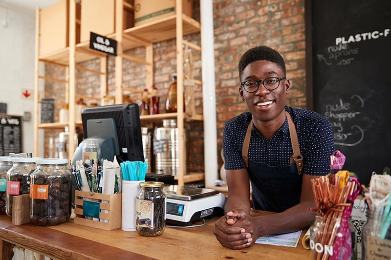 young male cafe worker smiling