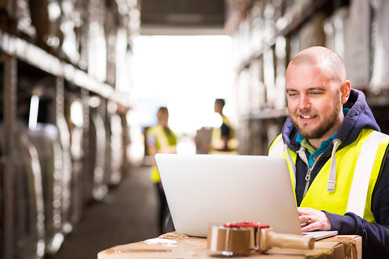 warehouse worker using his laptop computer