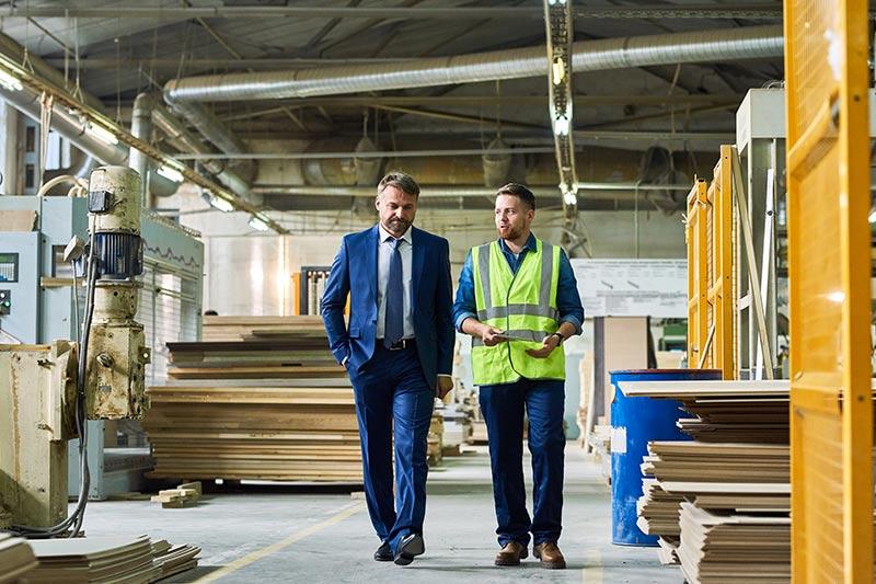 two businessmen walking in a warehouse