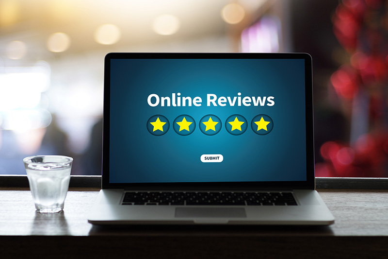 laptop showing online reviews with five stars