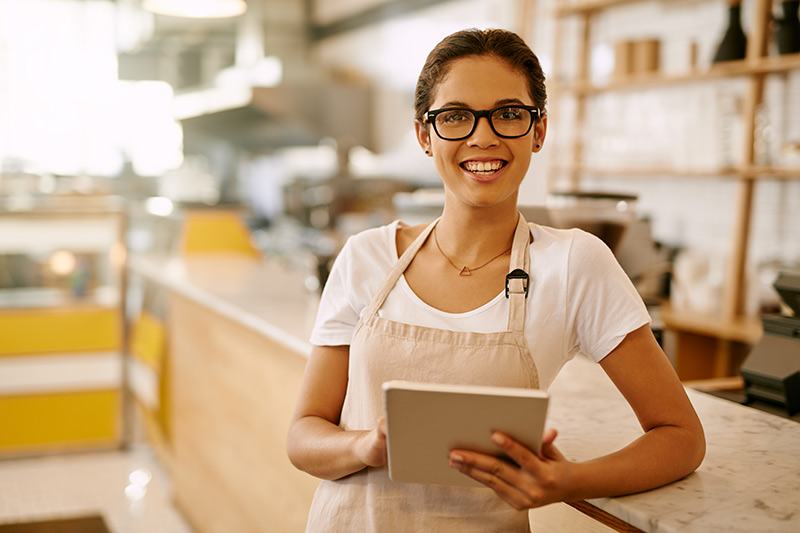 young female cafe owner smiling in front of a counter