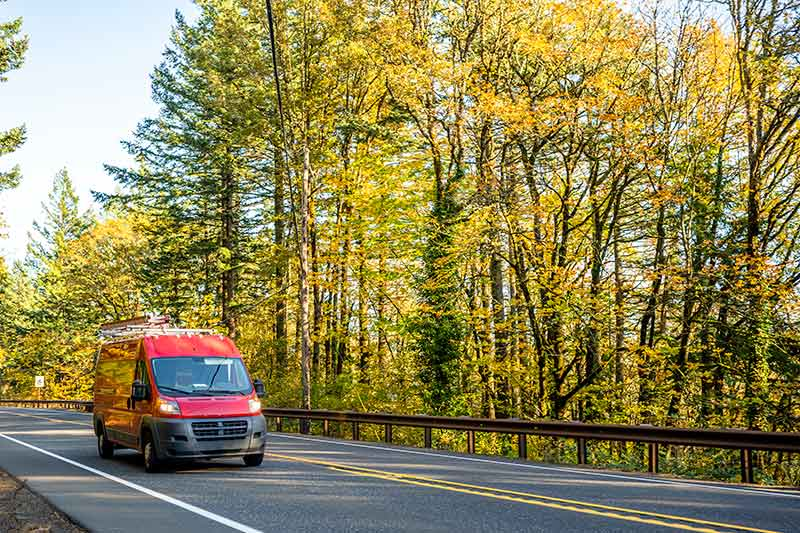 red business van on the highway near beautiful trees