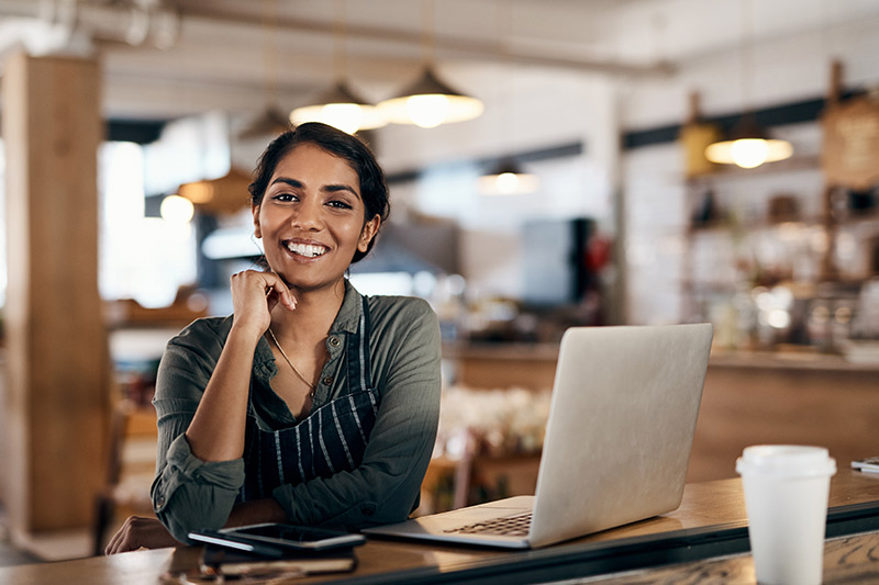 female business owner smiling in her coffee shop